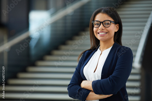 Fototapeta Smiling smart attractive young black lady in glasses standing in lobby and looking at camera, she working in prosperous company obraz