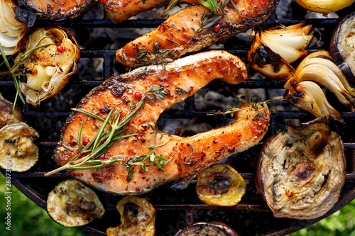Fototapeta Grilled fish, grilled salmon steak with the addition of rosemary, aromatic spices and vegetables on the grill plate outdoors, top view, close-up. Grilled seafood obraz