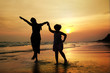 Mother and girl on the beach at sunset background