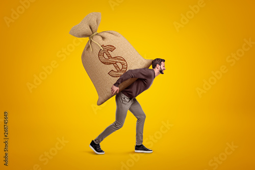 Side view of young handsome man in casual clothes carrying huge heavy sack with dollar symbol on Canvas Print