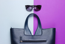 Leather Bag, Sunglasses On Gray-purple Background. Top View
