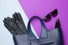 Leather Bag, Sunglasses, Gloves, Perfume Bottle On Gray-purple Background. Women's Fashion Accessories