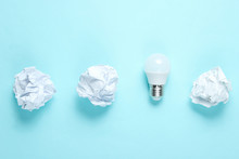Energy Saving LED Light Bulb And Crumpled Paper Balls On Blue Background. Minimalistic Business Concept, Idea. Top View