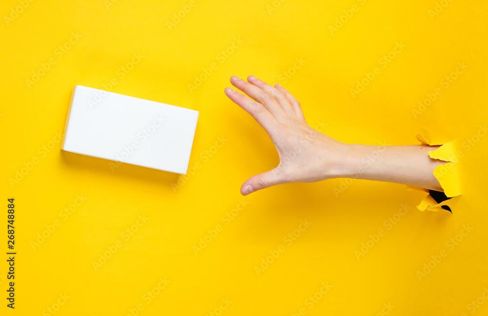 Fototapeta Female hand takes white box through torn yellow paper. Minimalistic creative fashion concept