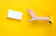 canvas print picture - Female hand takes white box through torn yellow paper. Minimalistic creative fashion concept