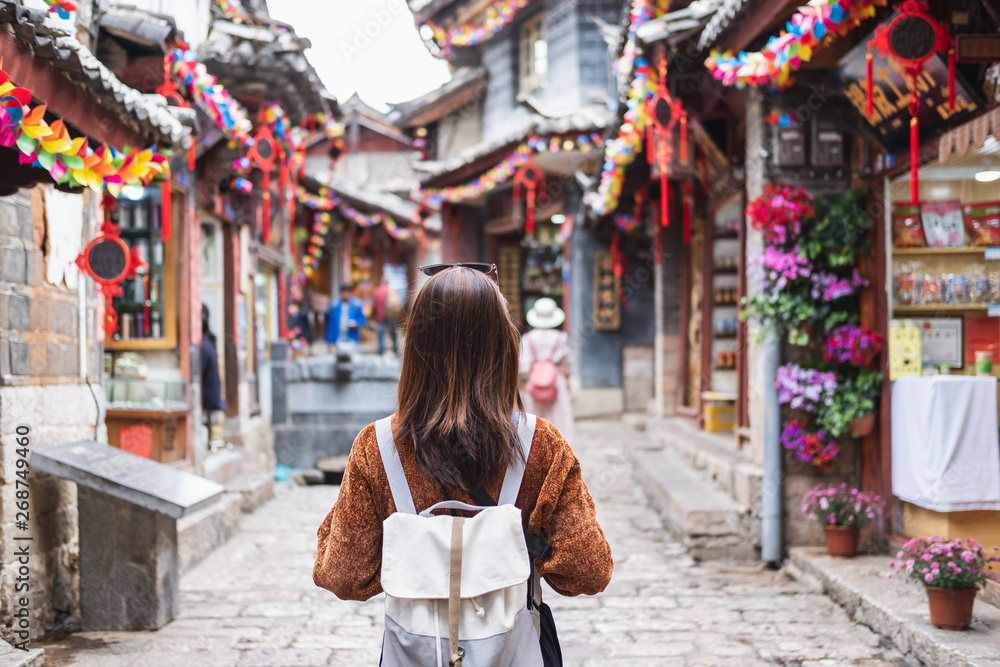Fototapeta Young woman traveler walking at lijiang old town in China, Travel lifestyle concept