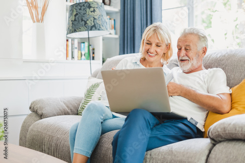 Fototapeta Couple senior using computer laptop on sofa at home for online shopping, surfing internet obraz