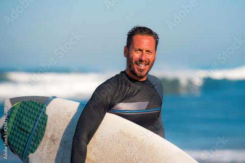 Photo natural portrait of attractive and happy surfer man on his 40s carrying surf boa