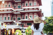 Woman Traveling With White Dress And Hat, Asian Traveler Looking To Buddha Tooth Relic Temple In Chinatown Of Singapore. Landmark And Popular For Tourist Attractions. Southeast Asia Travel Concept