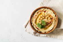Hummus Dip With Chickpea, And Parsley In Wooden Plate On White Background