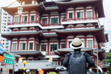 Man Hipster Traveling With Backpack And Hat, Solo Traveler Looking To Buddha Tooth Relic Temple In Chinatown Of Singapore. Landmark And Popular For Tourist Attractions. Southeast Asia Travel Concept