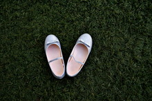 Silver Girl's Shoes With Ribbon On The Grass
