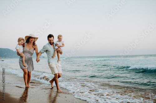 Photo  A family with two toddler children walking on beach on summer holiday at sunset