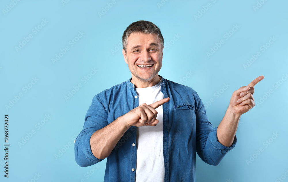 Fototapeta Handsome mature man pointing at something on color background