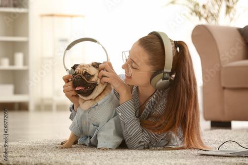 Obraz Teenage girl with cute pug dog listening to music at home - fototapety do salonu