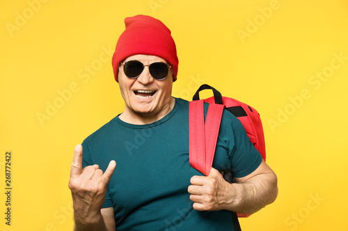 fototapeta na ścianę Portrait of stylish senior man showing devil horns gesture on color background