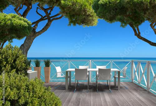 Billede på lærred Urlaub am Meer auf einer Terrasse mit Gartenmöbeln umrahmt von Bäumen - 3D rende