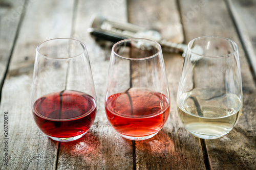 Fotomural WIne tasting concept - red, rose and white wine in glasses on wood background
