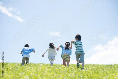 草原を走る小学生の後姿 Fototapet