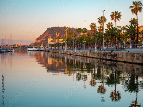 Foto auf Leinwand Lachs View of a promenade passing Port Vell in Barcelona during the sunrise.