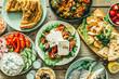 Leinwandbild Motiv Selection of traditional greek food - salad, meze, pie, fish, tzatziki, dolma on wood background, top view