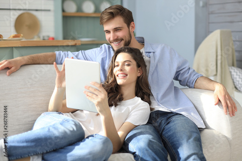Obraz Young couple watching media content online in a tablet sitting on a sofa in the living room. - fototapety do salonu