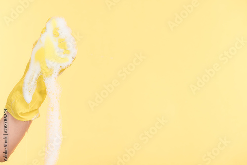 cropped view of cleaner in yellow rubber glove squeezing sponge with foam on yellow background