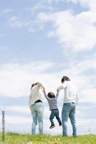 若い家族の全身後ろ姿、青空背景 Wall mural