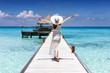Glückliche Frau in weißem Sommerkleid läuft auf einen Holzsteg über türkisem Meer auf den Malediven und genießt ihren Uraub