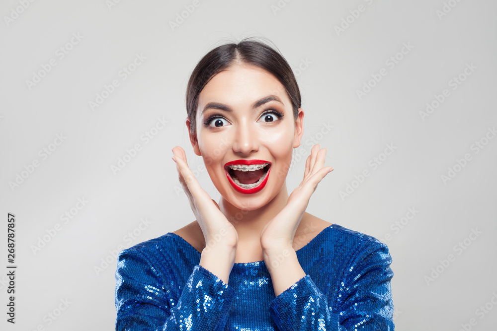 Fototapety, obrazy: Happy surprised woman in braces on teeth on white background. Excited girl with braces having fun