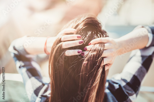 Fotografia  Back view of a brunette beauty coming through her wind swept hair with hands