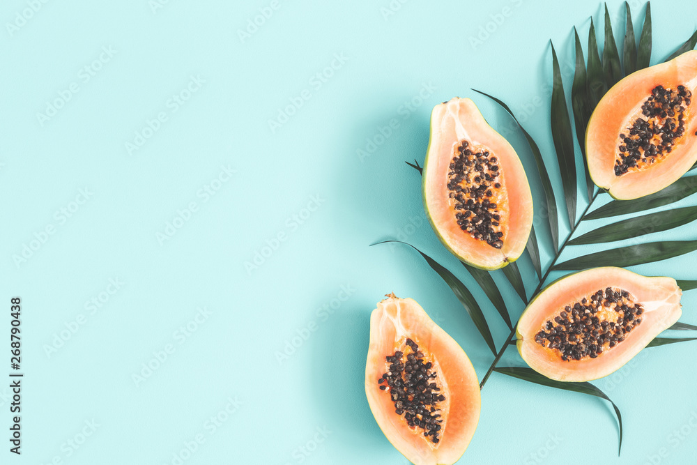 Fototapeta Summer fruits. Papaya and tropical leaves on blue background. Summer concept. Flat lay, top view, copy space