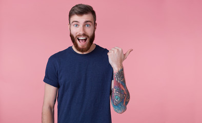 Young happy red-bearded young guy , with wide open mouth in surprise, saw something wrong, wants to draw your attention pointing finger to copy space at the right side isolated over pink background.
