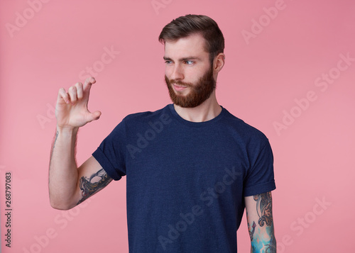 Obraz na plátně  Portrait of young attractive red-bearded guy, frowning, shows fingers something small and looks at it with a smirk and distrust isolated over pink background