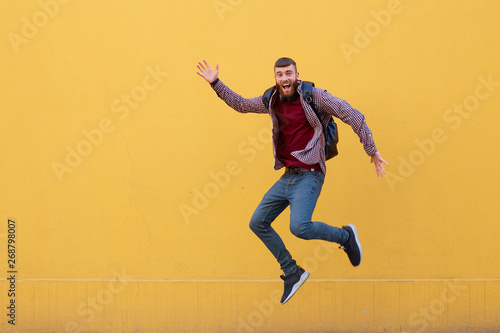 Aluminium Prints Superheroes Happy young attractive ginger bearded man jumping and waving his hand, wearing in basic clothes with backpack. Looking at the camera, smiling with wide open mouth, over a yellow wall with copy space.