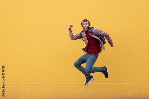 Aluminium Prints Superheroes Happy young handsome ginger bearded man jumping like superhero, full of energy, wearing in basic clothes with backpack. Looking at the camera with wide open mouth over a yellow wall with copy space.