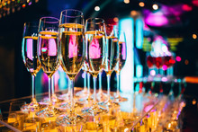 Full Glass Of Champagne In A Nightclub. Many Glasses Of Champagne On The Bar. Bubbles Of Champagne In A Glass.