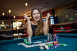 Leinwandbild Motiv Happy woman in casino with poker chips and cards