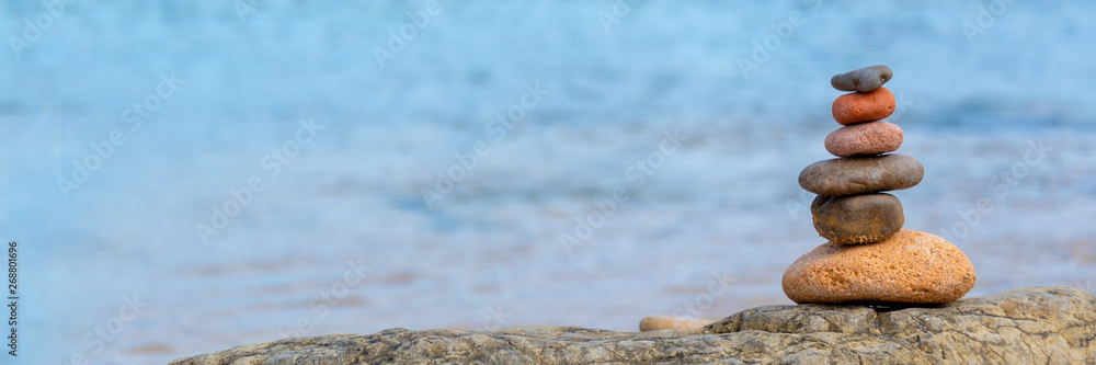 Fototapeta Pile of pebbles on a beach, panoramic blue water background, balanced stack of stone with copy space, zen web banner