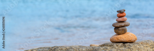 Pile of pebbles on a beach, panoramic blue water background, balanced stack of s Canvas Print