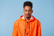 Close Up Of Uhappy Young African American Dark Skinned Man In Disgust, Dissatisfied With The Rainy Weather Outside, Wears In Orange Rain Coat, Frowns Isolated Over Blue Background.
