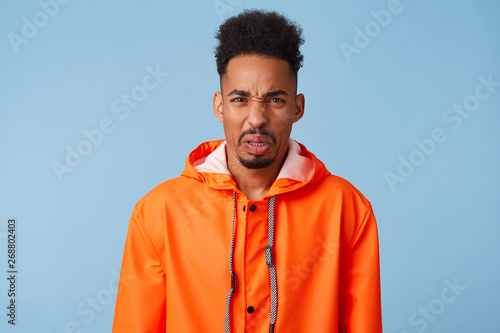 Valokuva  Close up of uhappy young african american dark skinned man in disgust, dissatisfied with the rainy weather outside, wears in orange rain coat, frowns isolated over blue background