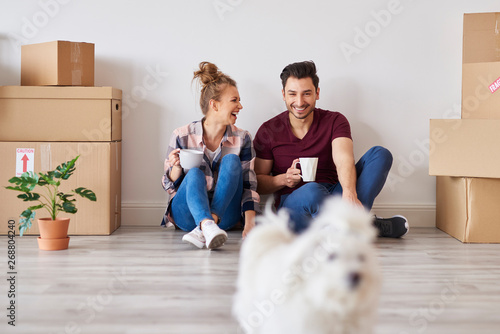 Cheerful couple with coffee cups relaxing in their new apartment - 268804240