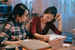 smart woman friend in glasses comforting to sad student with failed exam sitting in night home kitchen prepared for test again. two young girls studying in late midnight. lady consoling crying sister