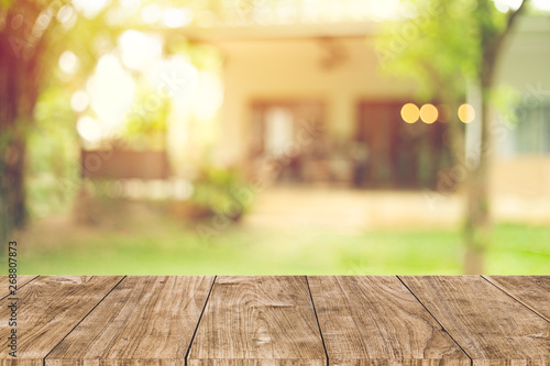 Foto wooden table space with green home backyard view blur background for advertising