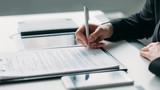 Modern business investment. Corporate relationship. Closeup of female hand signing contract. - 268808246