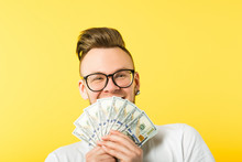 Happy Young Man Bearded Hipster Holding Dollar Cash Bunch Covering Mouth Hiding Behind Money. Generous Sum Salary.