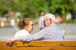 Senior couple wearing sunlglasses relaxing sitting on a bench in city park