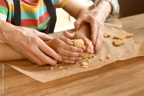 Little girl with her grandmother cooking cookies at table, closeup