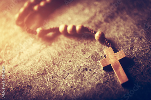 Fotografía Wooden rosary with cross on stone background.